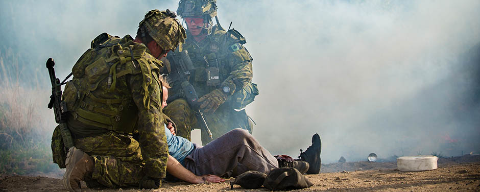 Slide - Members of the Royal 22e Régiment escort a civilian with simulated injuries