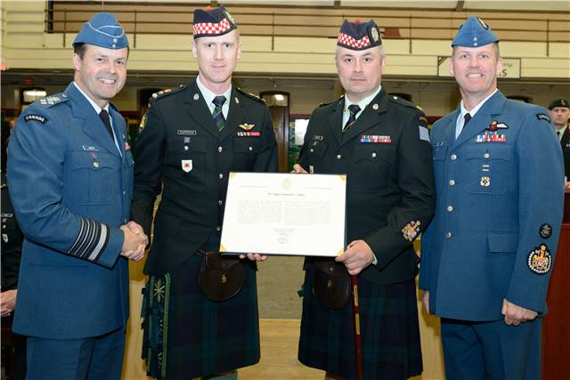 General Tom Lawson, Chief of the Defence Staff presents Lieutenant-Colonel Kyle Clapperton, Commanding Officer of The Calgary Highlanders, Chief Warrant Officer Chris Tucker, Calgary Highlanders and Chief Warrant Officer Kevin West, Canadian Forces Chief Warrant Officer with the Canadian Armed Force