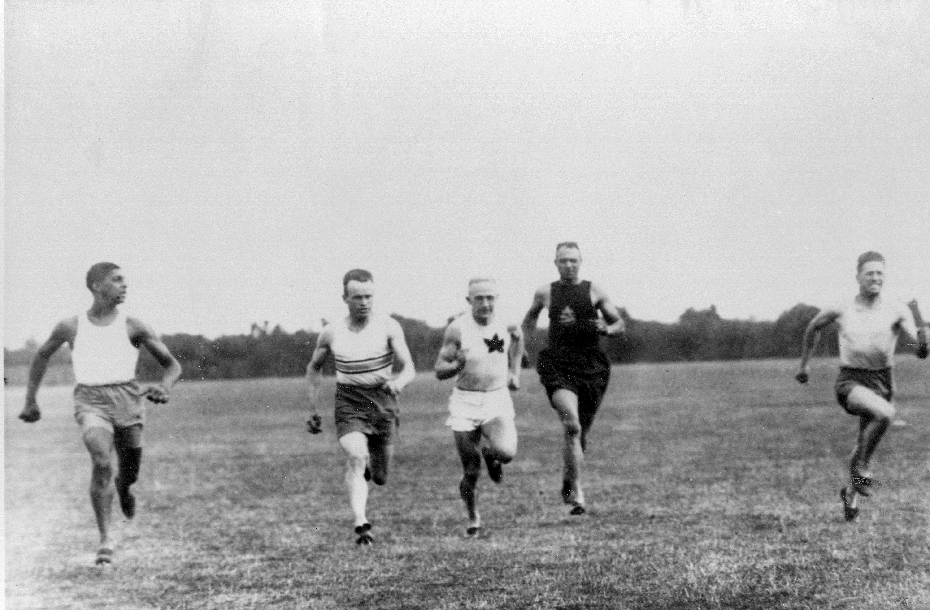 An antique black and white image of a group of five runners sprinting across an open field.