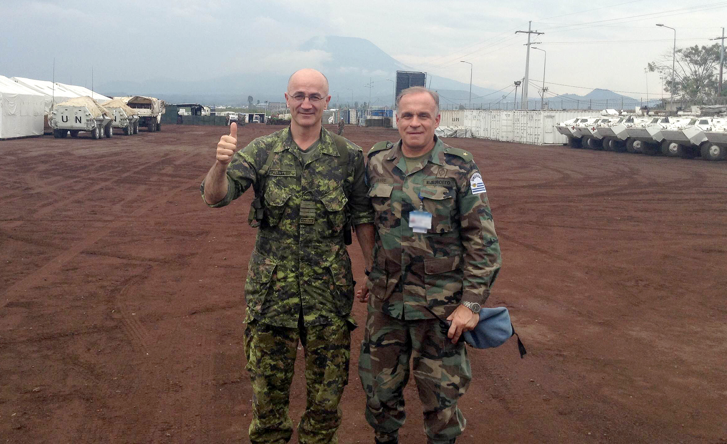 Two middle-aged men in camouflage army uniforms stand in an expansive parking area filled with white tents and white United Nations amoured personnel carriers.