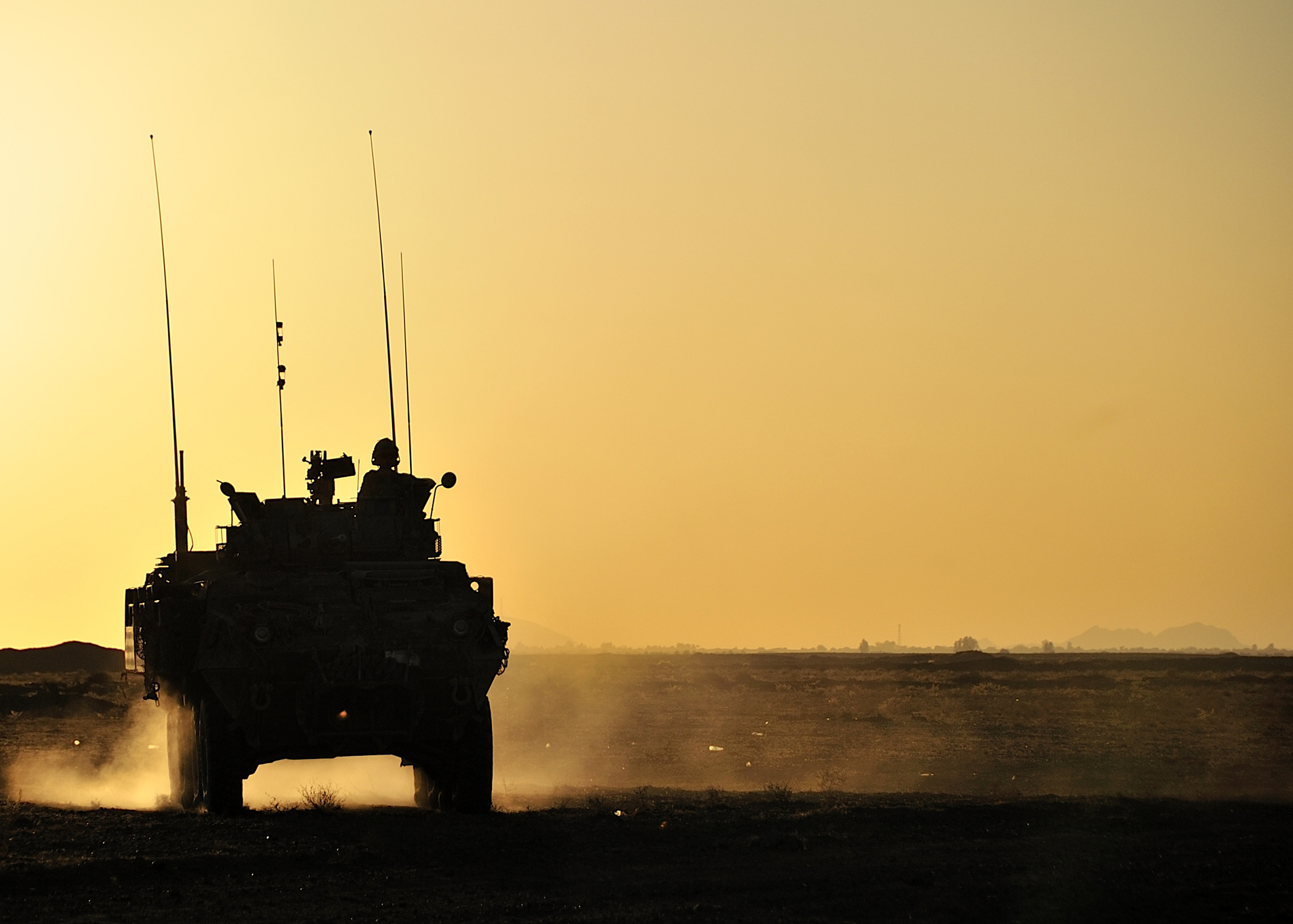 A silhouette of a LAV III is seen driving across an Afghani desert at sun down.