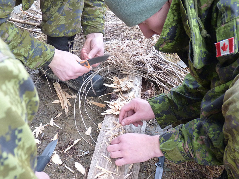 Soldiers of The Canadian Scottish Regiment (Princess Mary's) use a knife, flint, and tinder to spark a fire during Exercise Coastal Sasquatch at Mount Washington on Vancouver Island. 