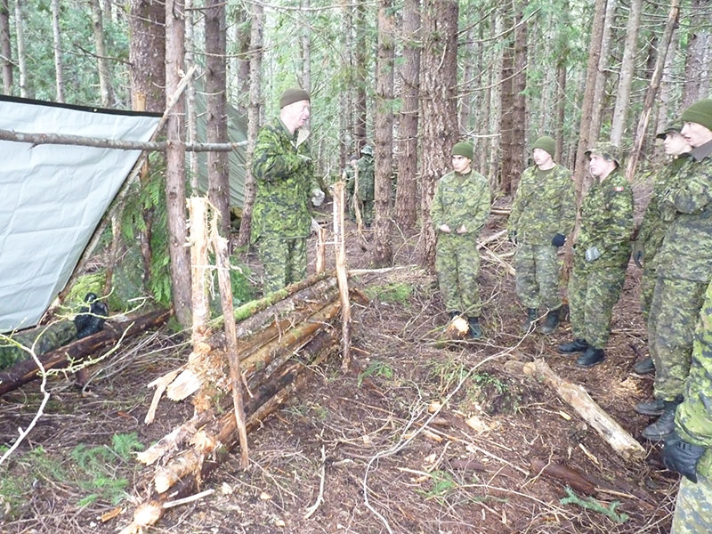 Sergeant David Coull (left) of The Canadian Scottish Regiment (Princess Mary's) demonstrates how to build a lean to shelter with a heat reflecting barrier during Exercise Coastal Sasquatch at Mount Washington, British Columbia. 