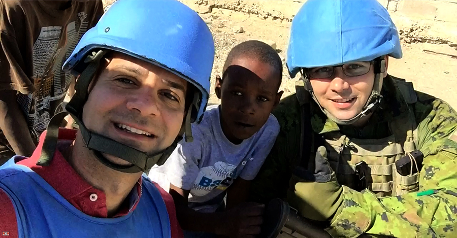 Maj Jérôme Robin-Thériault (right), of Operation HAMLET, and journalist Marzio Lorenzo of Brazil's Globo News interact with local children during a January 7, 2015 foot patrol in the Cité Soleil quarter of Port-au-Prince. Maj Robin-Thériault is currently embedded with a Brazilian battalion (BRABAT)