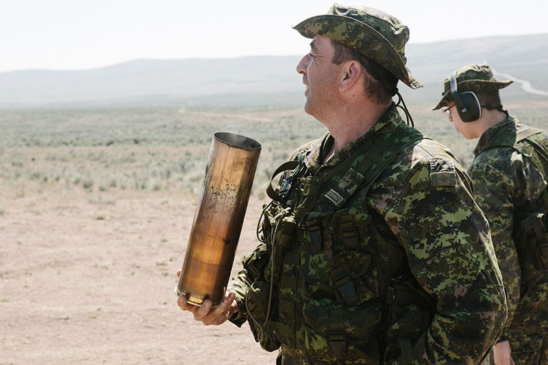 Warrant Officer Smith from the 15th Field Artillery Regiment RCA, smiles as he collects a casing after firing his last round. Photo: Bombardier Albert Law
