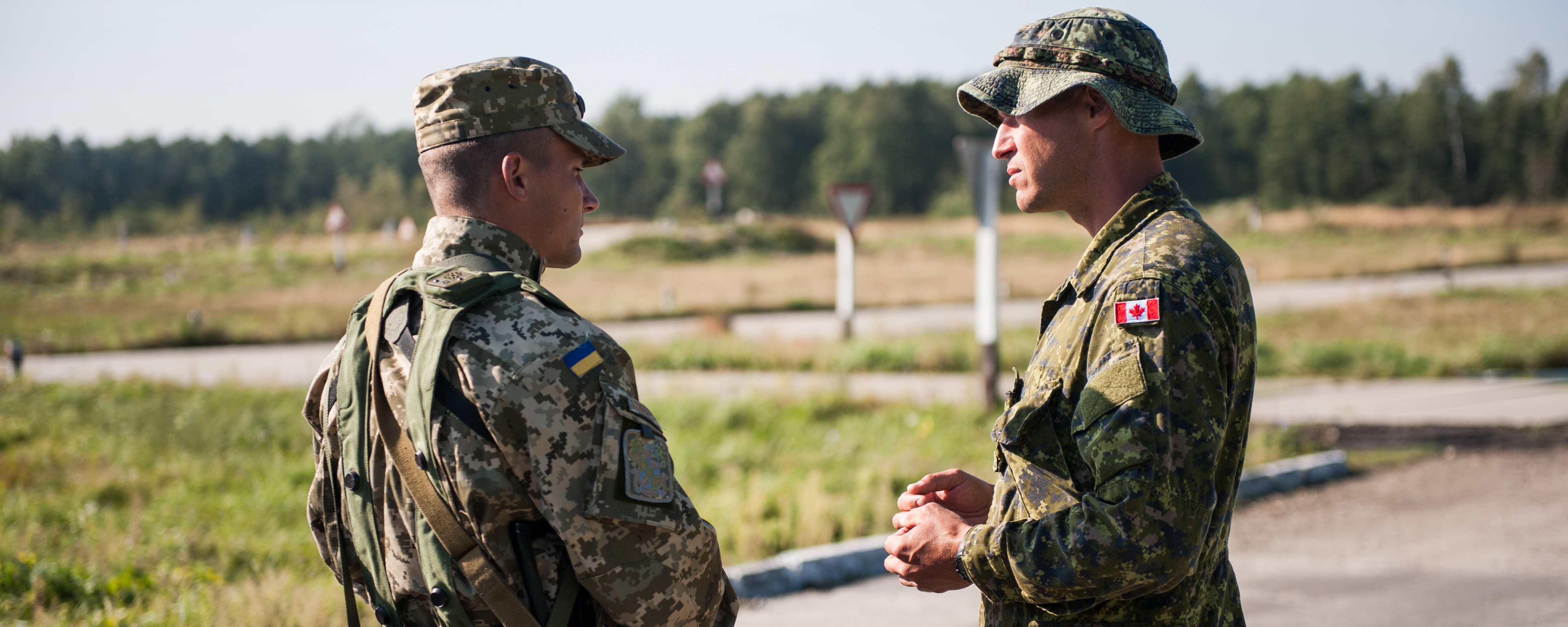 Slide - Two soldiers dressed in combat camouflage, one from the Canadian Army and the other from the Ukraine Army, are standing outside in a field of grass having a conversation.