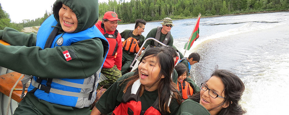 Slide - A group of young Aboriginal people are travelling on water in a speed boat which is being piloted by two adult male Rangers of the Canadian Army