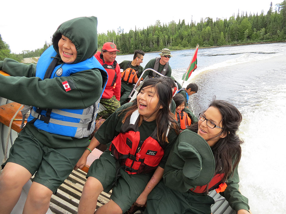 A group of young Aboriginal people are travelling on water in a speed boat which is being piloted by two adult male Rangers of the Canadian Army.