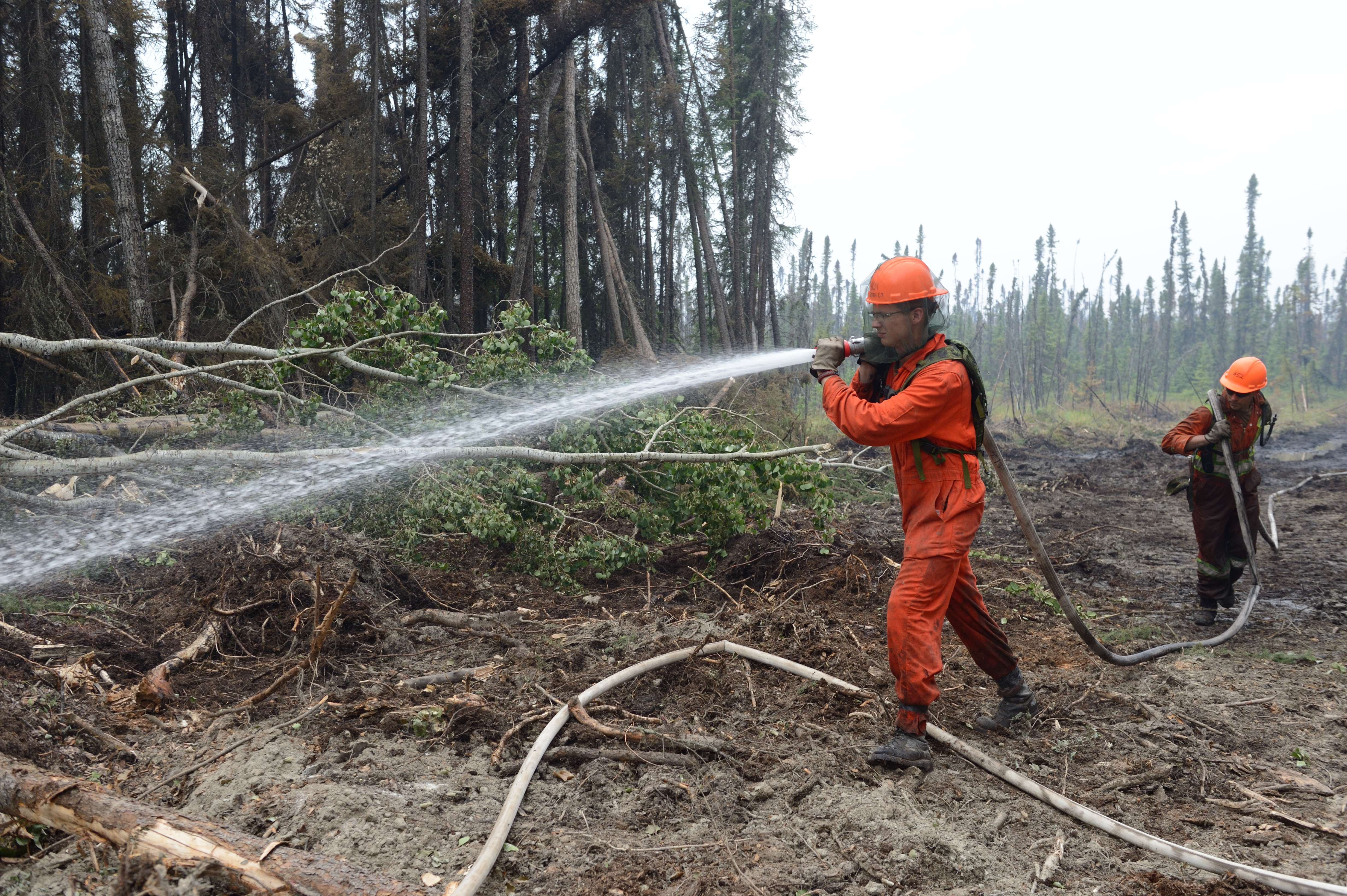 Two Canadian Army Reserve soldiers dress in orange coveralls are pulling a fire hose through a burned out forest, aiming a stream of water from the hose at the ground to extinguish hot spots.