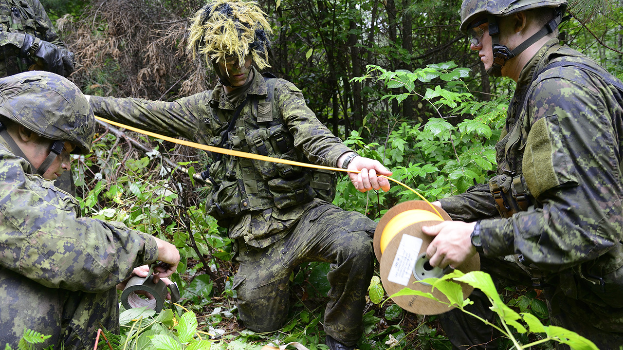 Sapper John Hiebert, Corporal Chase Kilbourne, and Sapper Chase Hannenburg of 31 Combat Engineer Regiment (The Elgin's) cut detonating cord for initiating the Manufactured Charges (Beehives) during Exercise STALWART GUARDIAN on August 20, 2015 at Garrison Petawawa, ON.