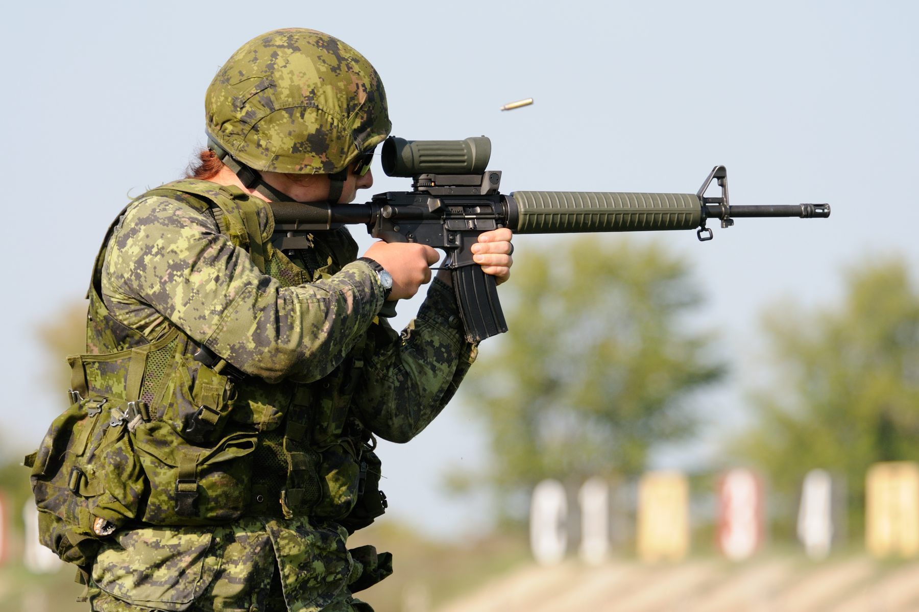 A female Canadian Army soldier dressed in camouflage combat gear shoots an assault rifle on a shooting range.