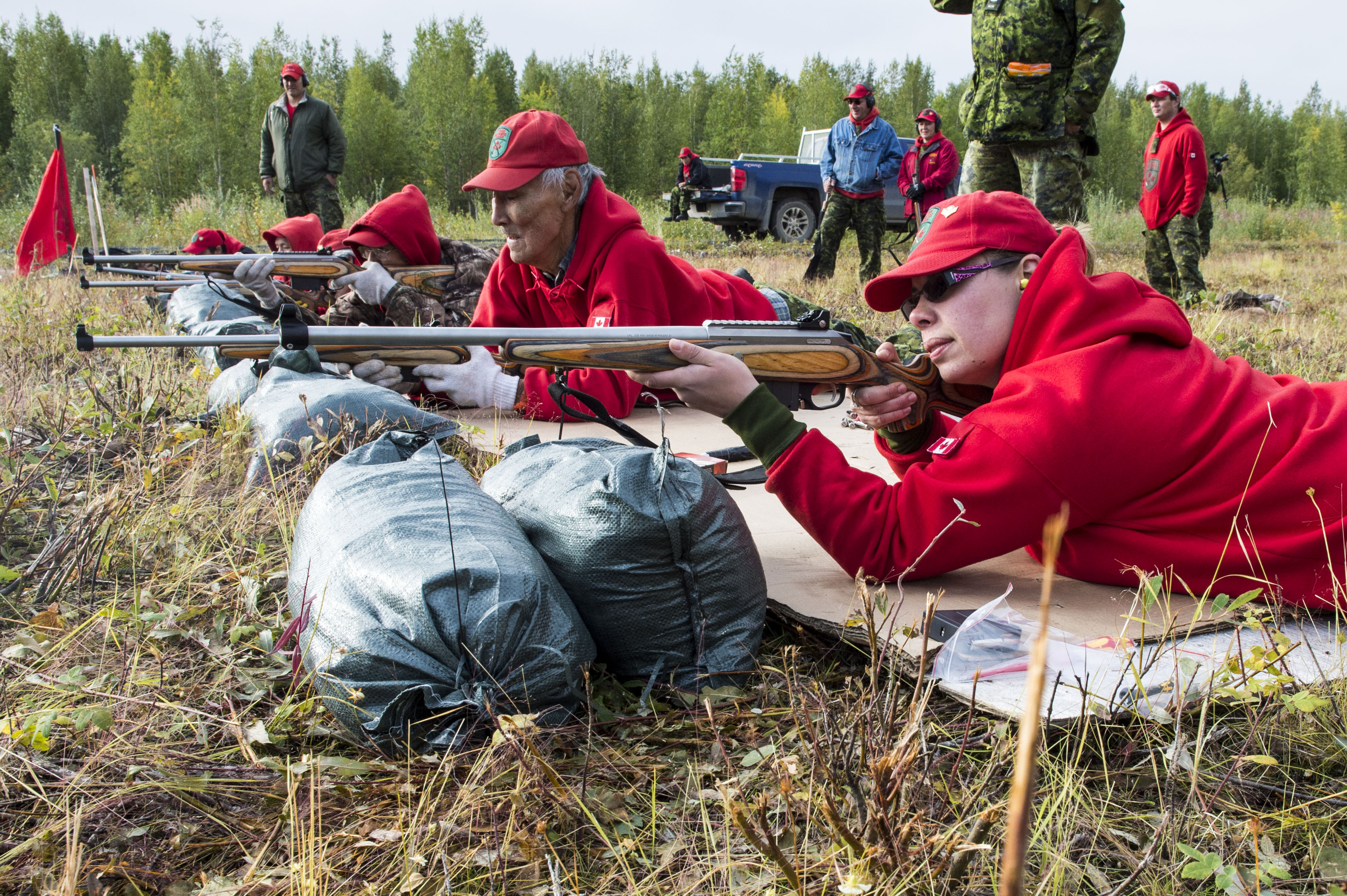 A group of six members of the Canadian Rangers dressed in red baseball caps and red hooded sweatshirts lay on the ground and aim long, wood-stocked rifles down a firing range.
