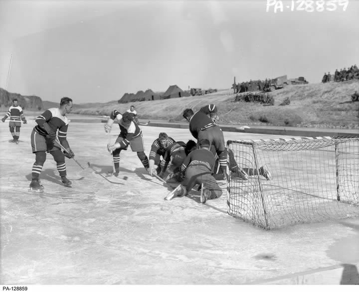 A black and white image from the nineteen-fifties of a group of men playing hockey on a frozen river.