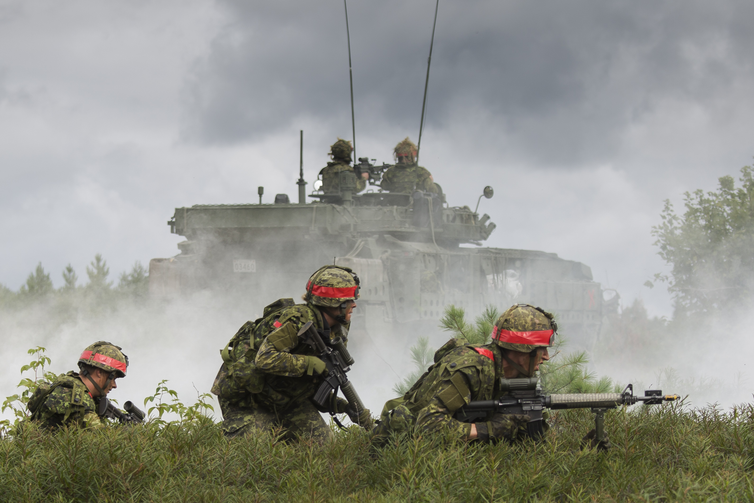 Simulated opposing force soldiers attack a defensive position occupied by the Canadian Army Reserve from 4th Canadian Division during Exercise STALWART GUARDIAN on August 26, 2015 at Garrison Petawawa, ON.