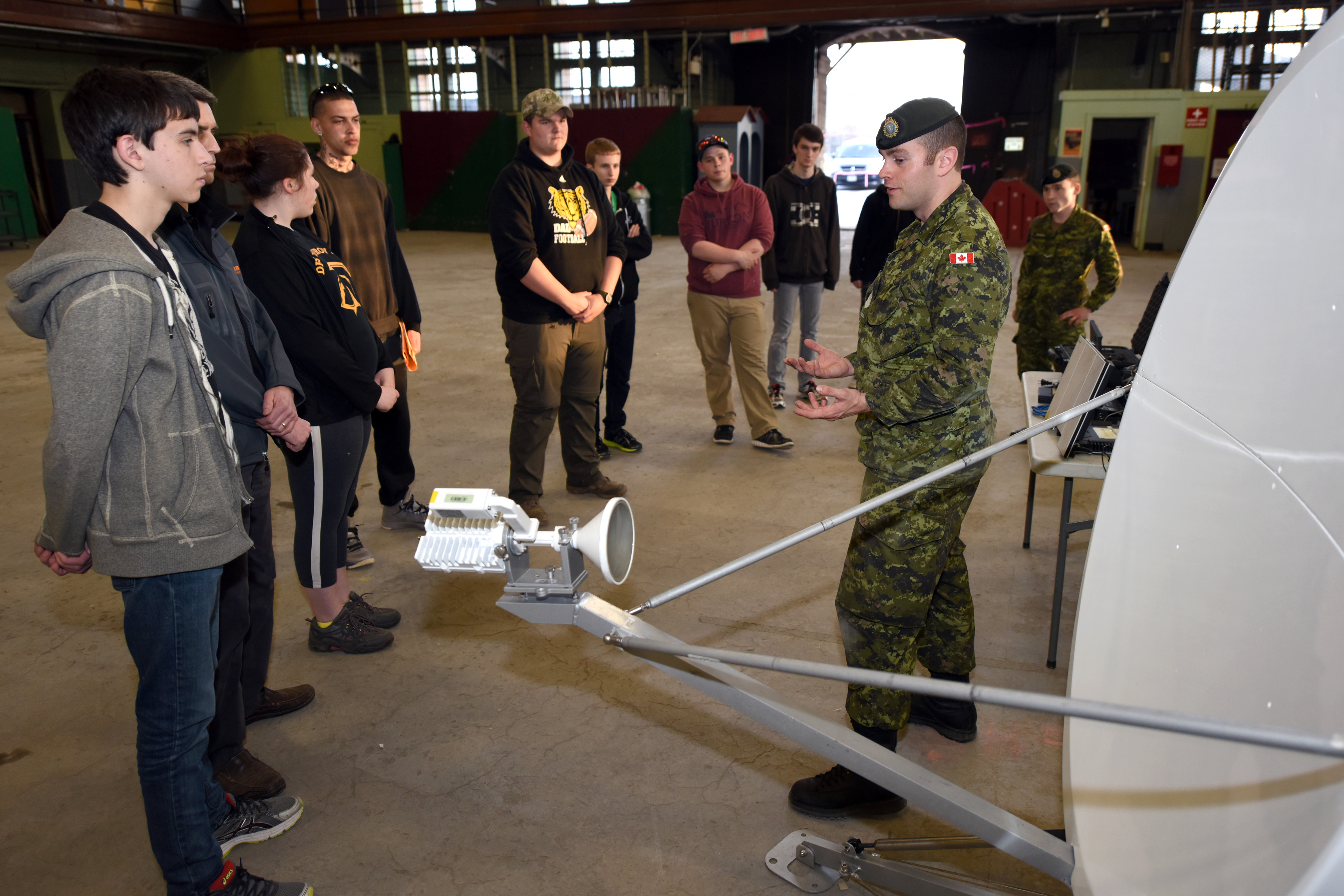 Sergeant Gordon Cummings, Regiment Training Sergeant and Private Zachary Cameron, a radio operator, both with 36 Signals Regiment in Halifax, Nova Scotia, describe a satellite communications dish to a group of candidates during the Army Civilian Engagement program in the Halifax Armouries on May 7, 2015.