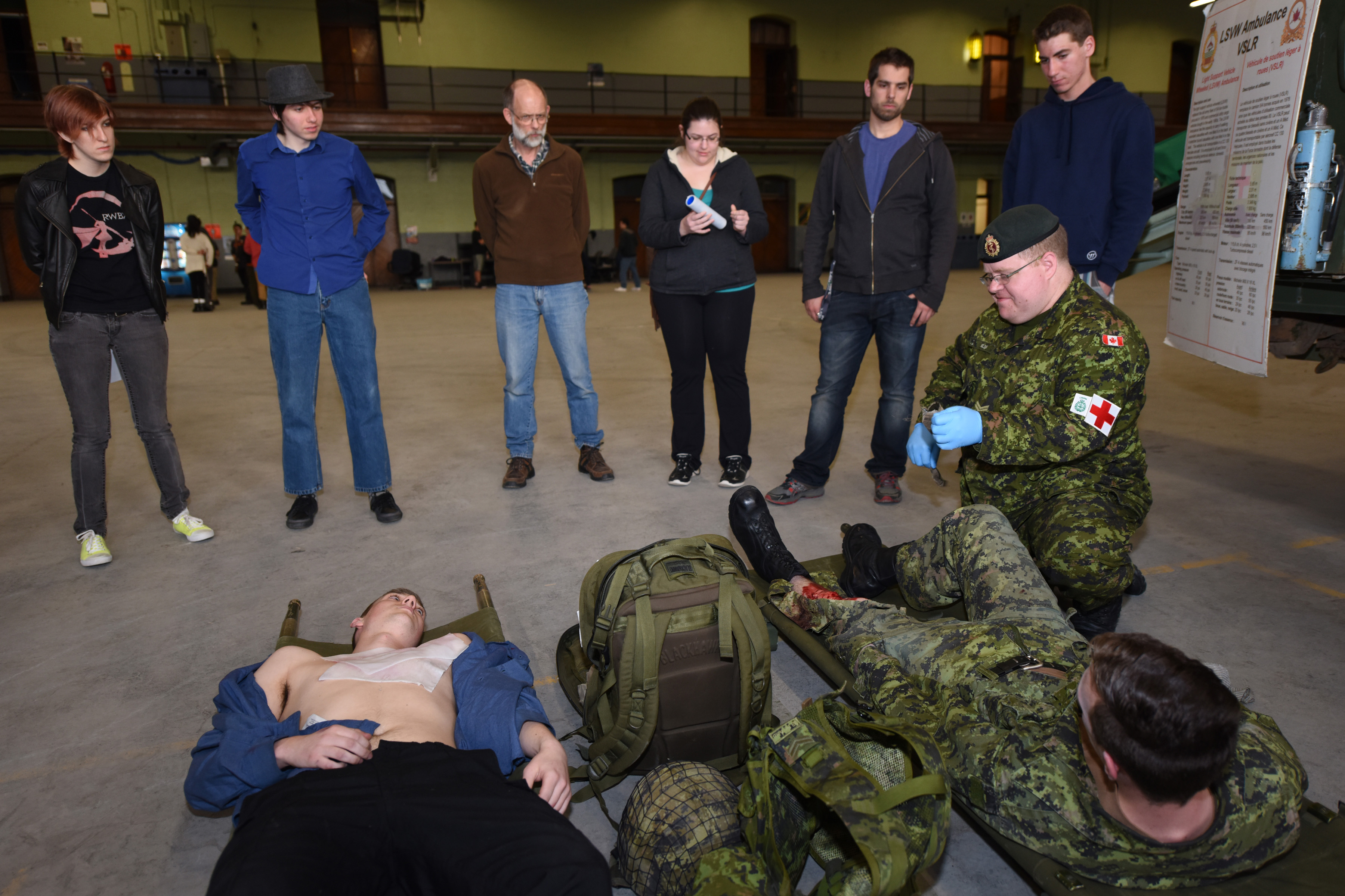 Corporal Russel Nelson, a medic with 33 Field Ambulance in Halifax, Nova Scotia, demonstrates the application of a field dressing to a simulated injury before a group of Army Civilian Engagement Program candidates in the Halifax Armouries on 7 May 2015.
