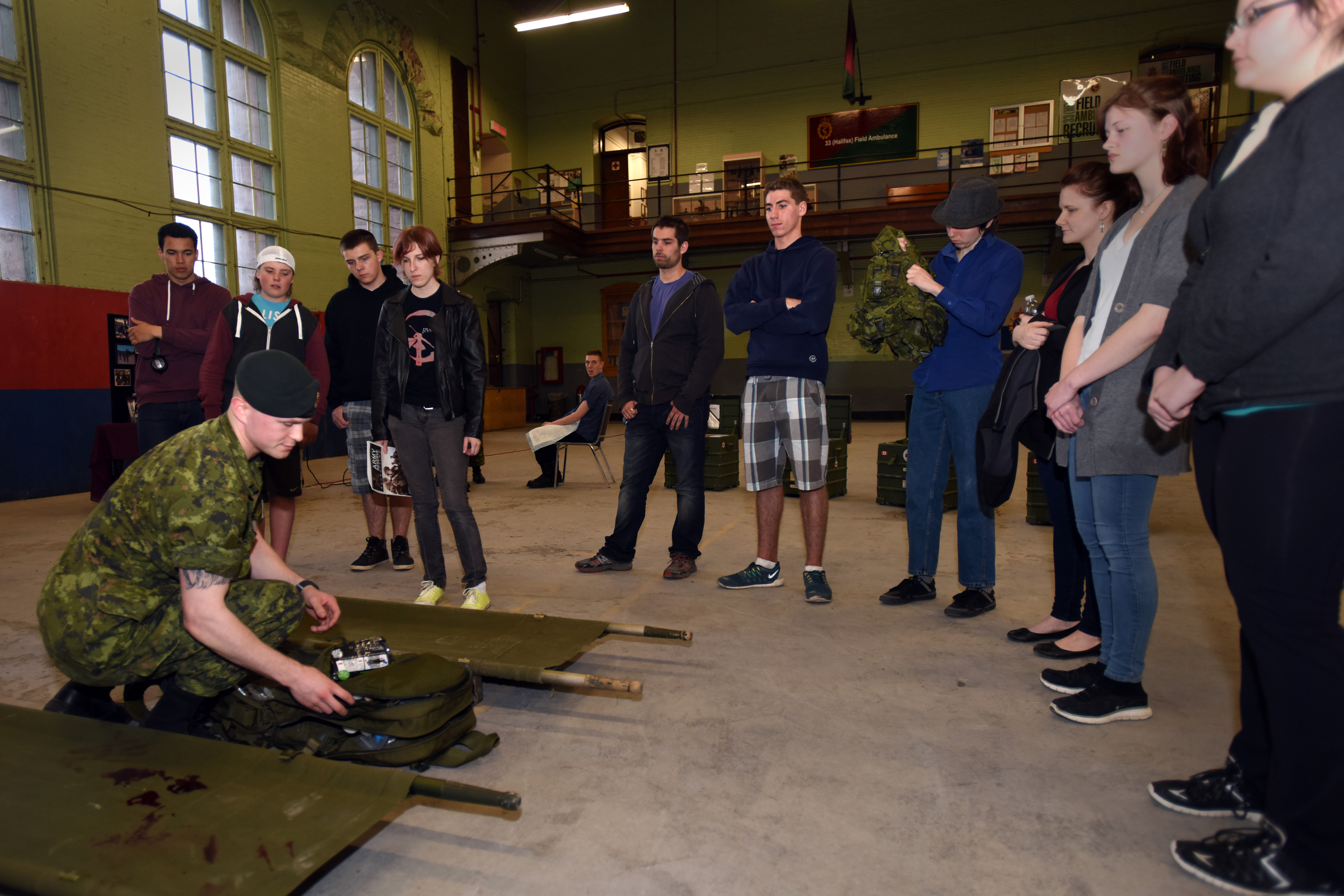 Corporal Bradley DeGrunchy, a medic with 33 Field Ambulance in Halifax, Nova Scotia, talks about a medic's kit bag to candidates of the Army Civilian Engagement program in the Halifax Armouries on May 7, 2015.