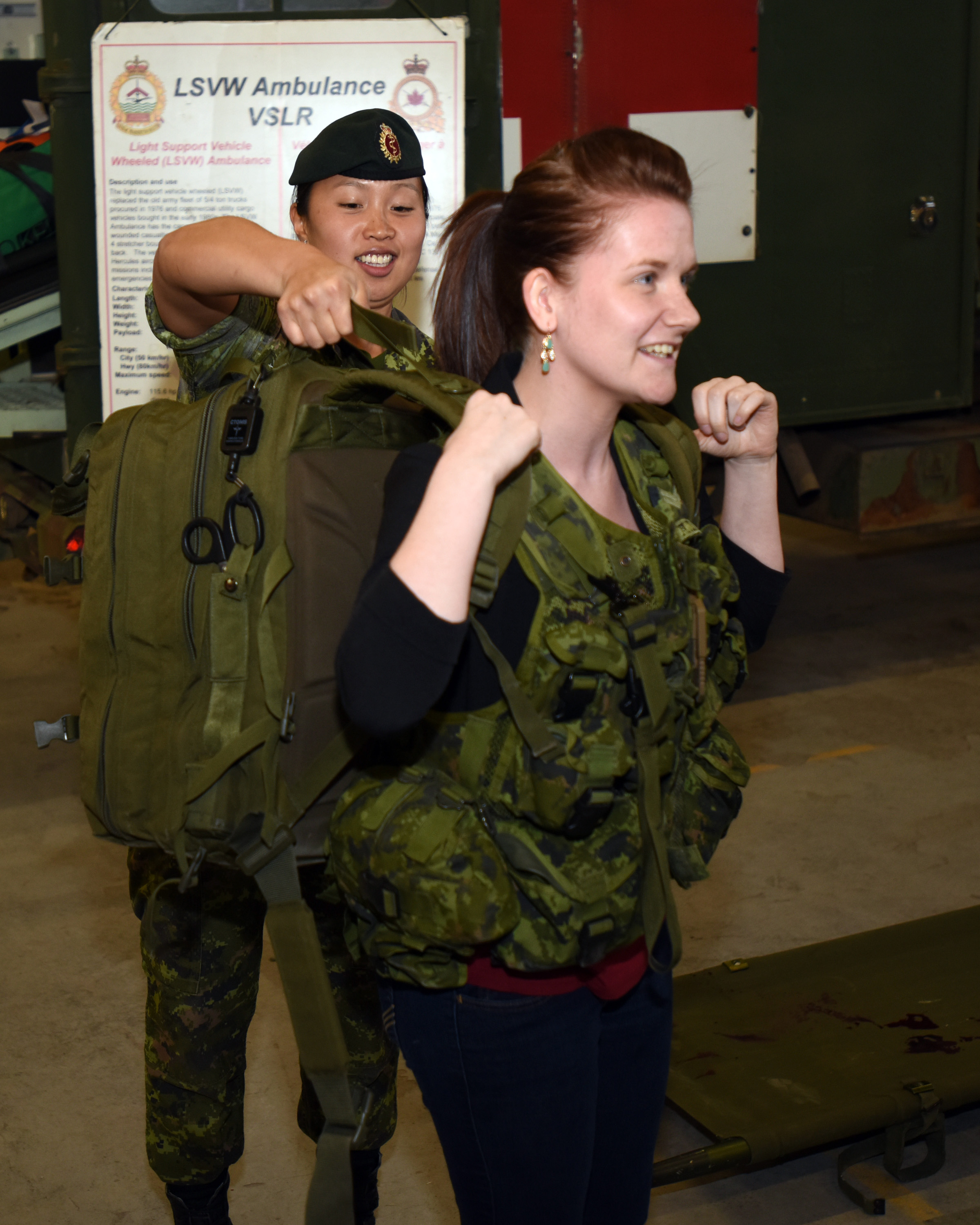 Sergeant Bo-Ram Hong, a medic with 33 Field Ambulance in in Halifax, Nova Scotia, loads up a candidate with the ACE program with a Medic's Kit bag and a Tactical Vest during a demonstration in the Halifax Armouries on 7 May 2015.