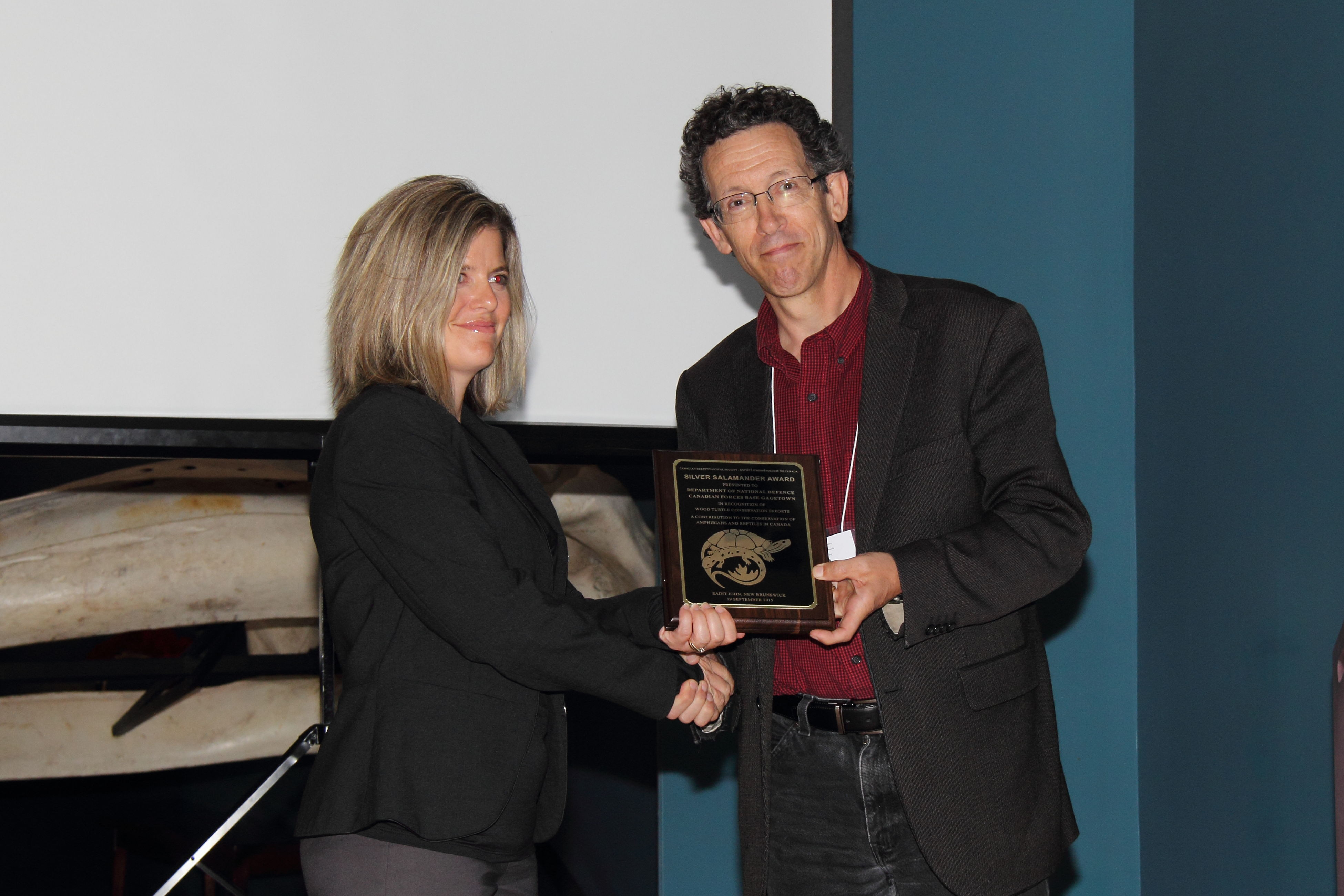 Dr. Don McAlpine, Head Curator of the New Brunswick Museum, presents the Silver Salamander Award to Deanna McCullum, Range Biologist at 5th Canadian Division Support Base Gagetown at the Annual Meeting of the Canadian Herpetological Society on September 19, 2015 in recognition of the base's contribution to the conservation of Wood Turtles. Photo by: Joe Crowley.