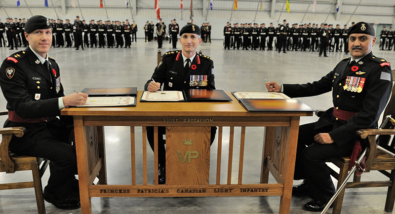 Colonel T.J. Cadieu, Commander 1 Canadian Mechanized Brigade Group (centre), oversees the official signing of the certificates signifying the Change of Command of 1st Battalion, Princess Patricia's Canadian Light Infantry from Major H.J. Mandaher (right) to Lieutenant-Colonel L.W. Rutland (left) on November 5, 2015 at the Edmonton Garrison. Photo: MCpl FriedaVanPutten