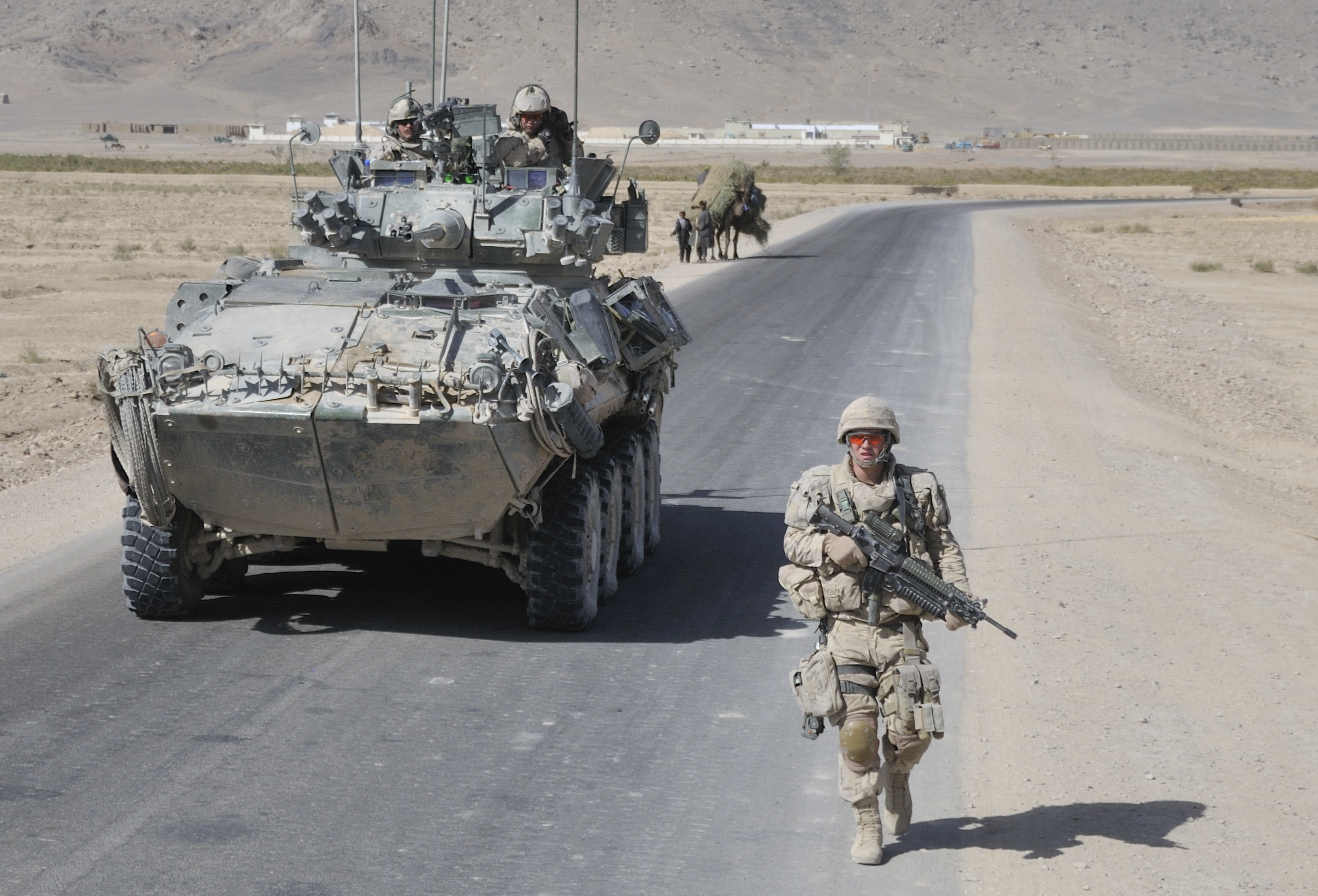 Corporal Rich Varey, Reconnaissance Squadron, the Royal Canadian Dragoons attached to 1st Battalion, The Royal Canadian Regiment Battle Group, walks alongside a COYOTE armoured reconnaissance vehicle, in the Panjwa'i District of Kandahar Province. Photo by: Corporal Shilo Adamson, Canadian Forces Combat Camera. ©2010 DND-MDN Canada.