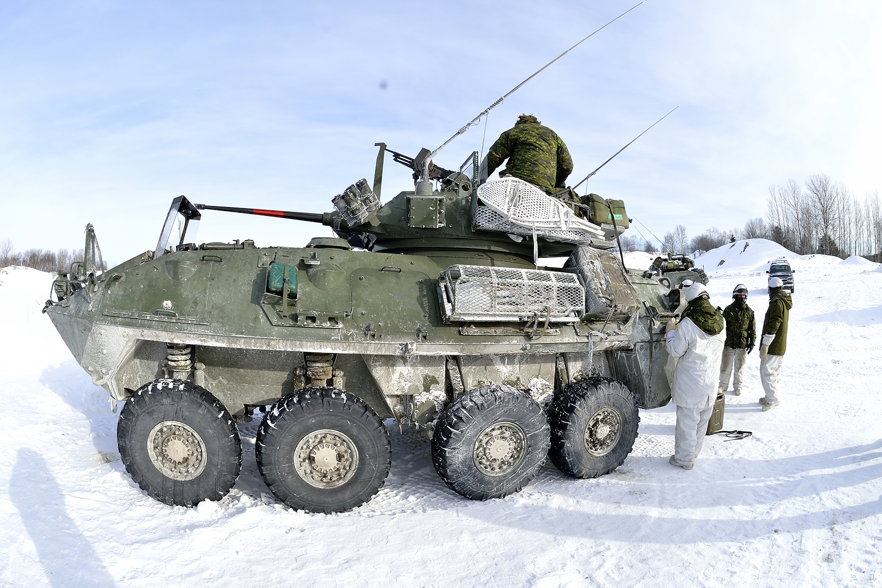Members of 21 Troop load a COYOTE armoured reconnaissance vehicle.