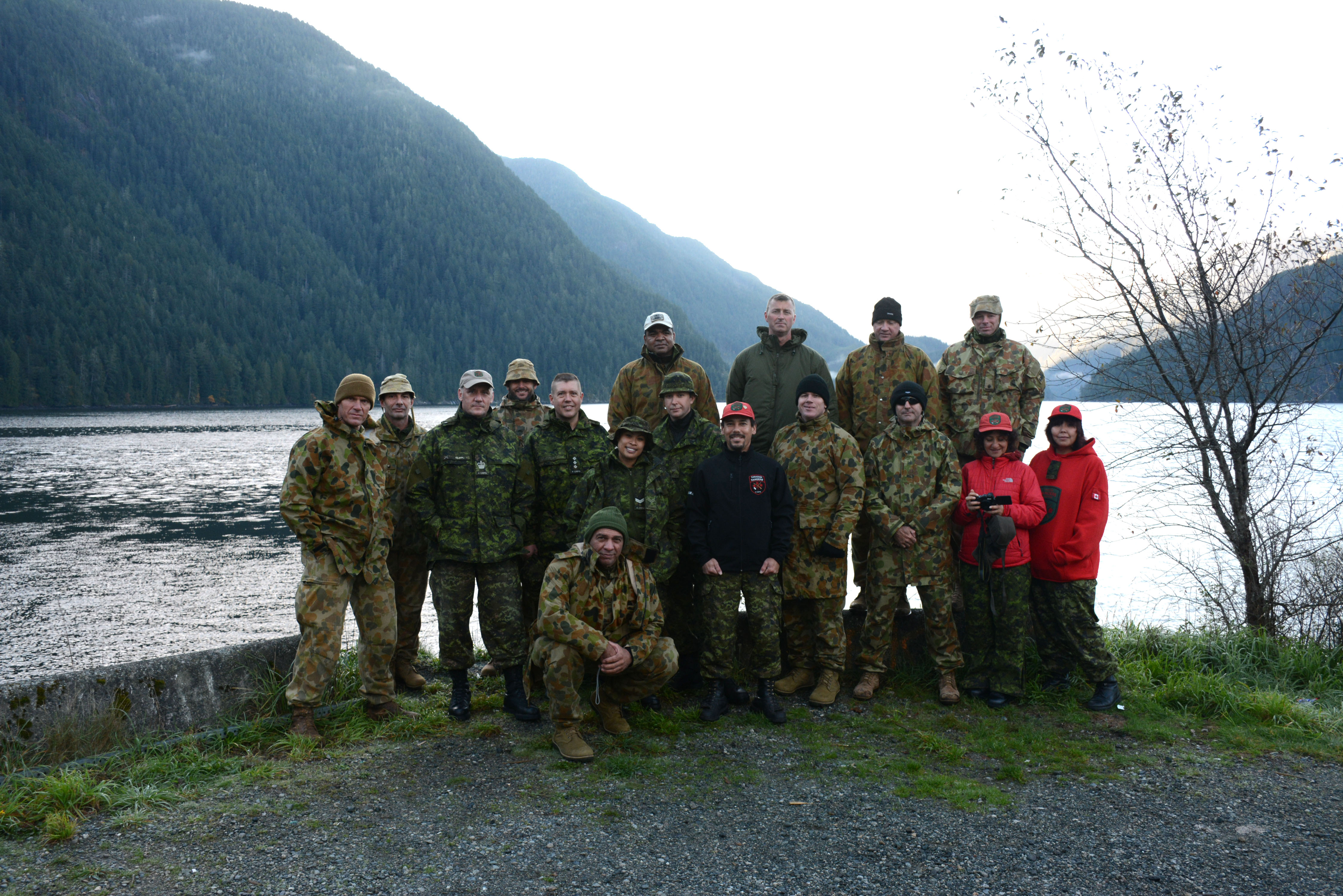 A group of 17 soldiers dressed in camouflage from Australia and Canada pose for a photo in front of a lake and montains.