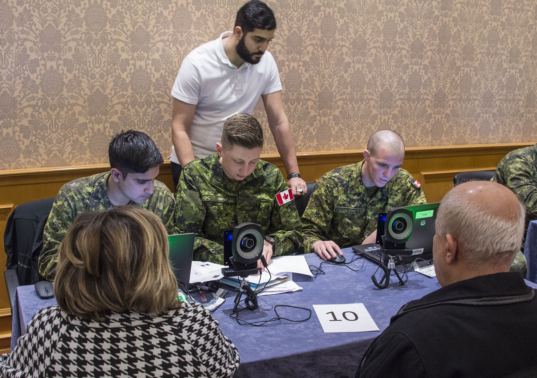 Three male soldiers dressed in camouflage and one civilian male are at a table interviewing a male and female refugee claimant.