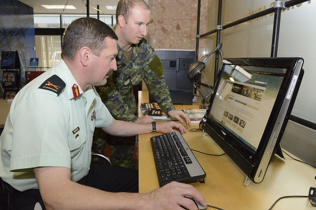 Brigadier-General Rob Roy MacKenzie speaks with Sergeant Nathan Smith while he browses a webpage.