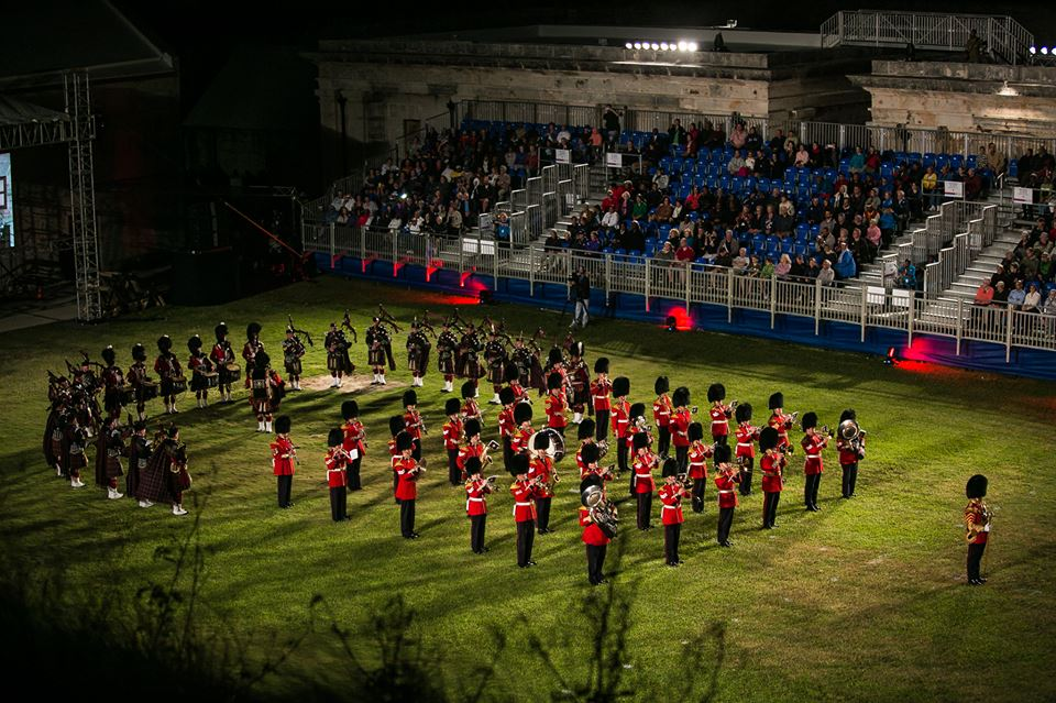 The Regimental Band of the Governor General's Foot Guards and the Pipes and Drums of the Cameron Highlanders of Ottawa (Duke of Edinburgh's Own) perform a choreographed sequence of marching, singing, Celtic bands, bagpipes and video footage during the open dress rehearsal of the 2015 Bermuda Tattoo at the Royal Dockyards in Mangrove Bay, Bermuda. The Regimental Band of the Governor General's Foot Guards was in Bermuda from 18 – 25 October to participate in the 2015 Bermuda Tattoo and to celebrate the 50th Anniversary of the Royal Bermuda Regiment. Photo by:  Mark Andrew Boughton.