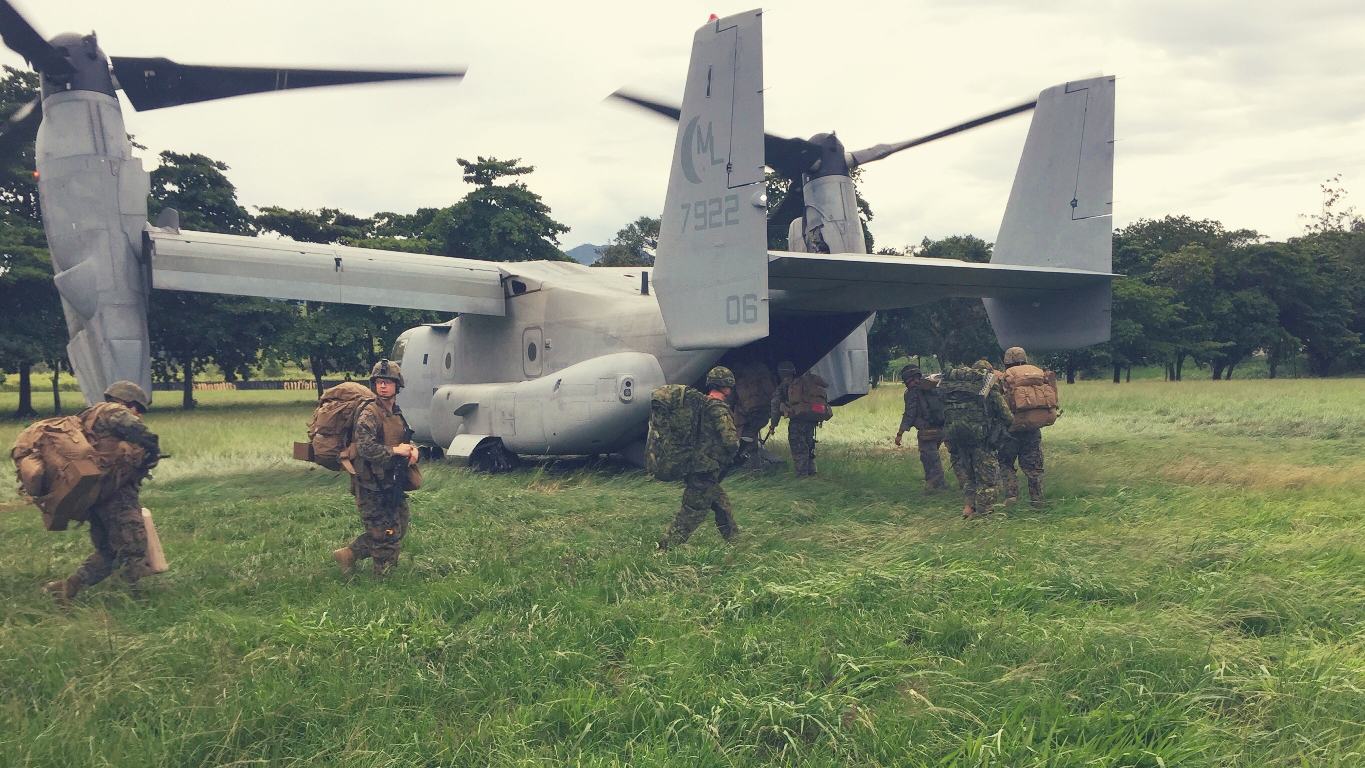 Soldiers and Marines climb on board a Boeing VH-22 Osprey.
