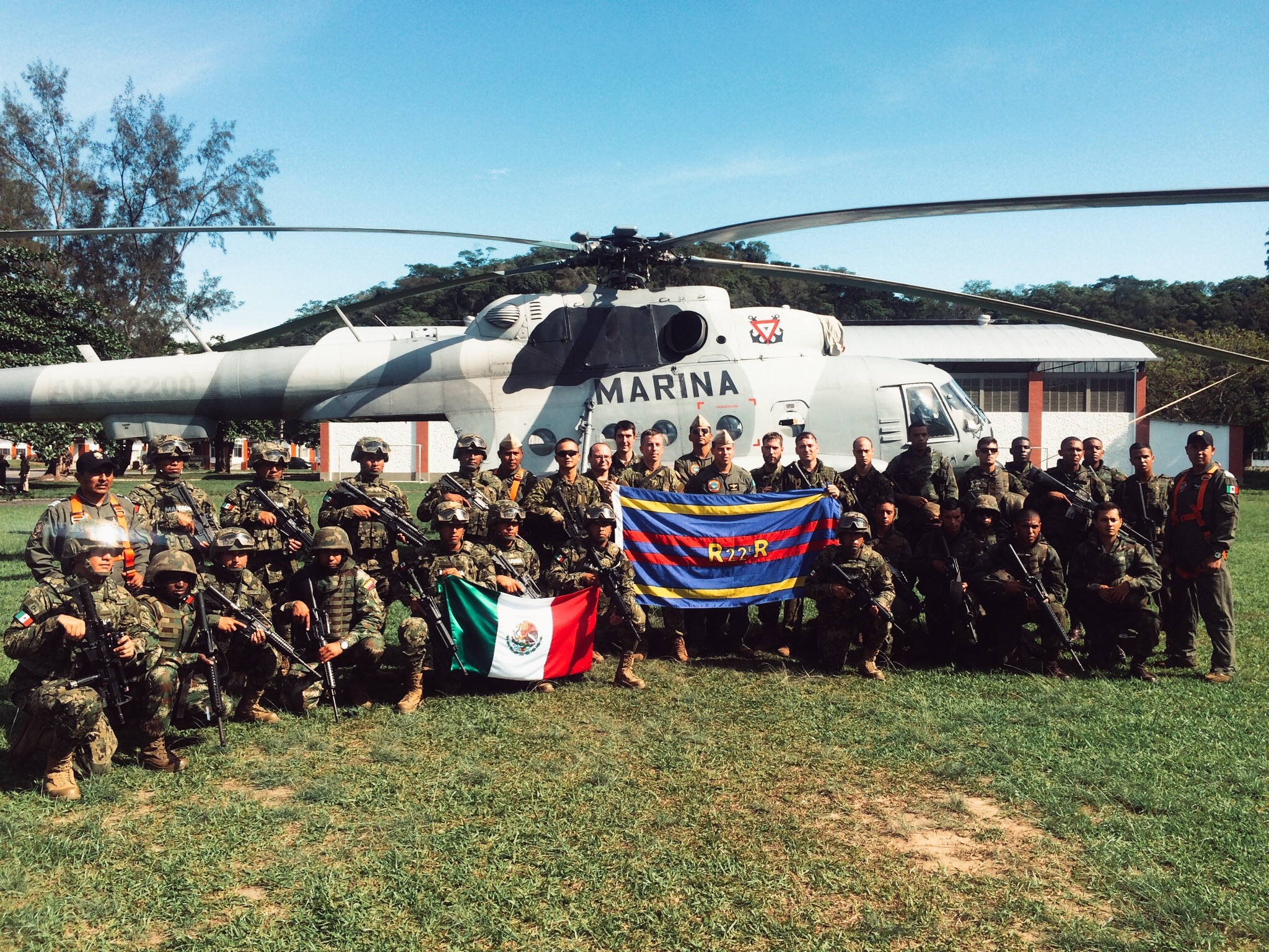 Participants from Canadian, Mexican, and Brazilian delegations proudly display their colours in front of a MI-17 Hip helicopter from the Mexican Navy during the South American exercise UNITAS-AMPHIBIOUS held in Brazil from November 14 to 25, 2015. Photo by: Capt Ken Wang, 2nd Batallion, Royal 22e Régiment. ©2015 DND-MDN Canada.