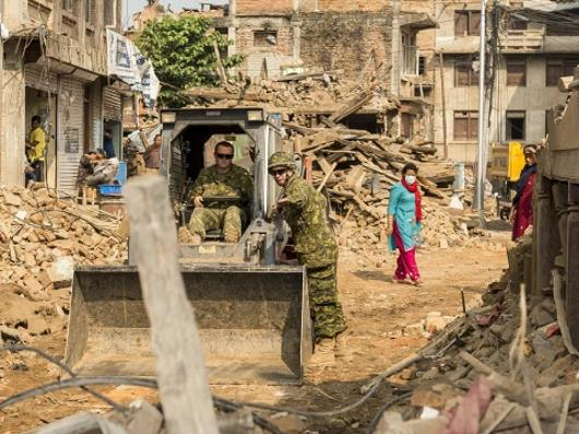 Corporal Jason Taylor and Sapper Joseph Vanexan, 4 Engineer Support Regiment, clean a street in Sankhu, Nepal on May19, 2015. Photo by: MCpl Cynthia Wilkinson, Canadian Forces Joint Imagery Center. ©2015 DND-MDN Canada.