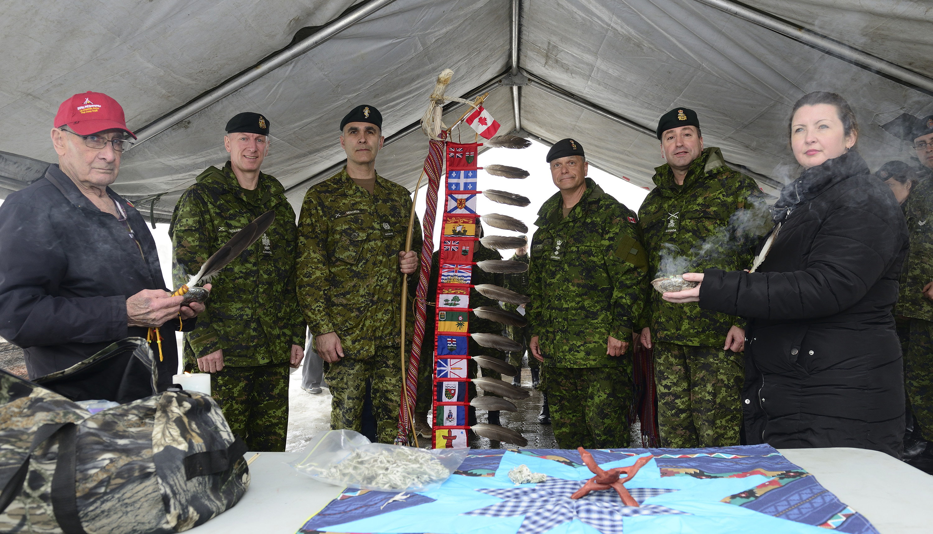 Five men - four of them dressed in camouflage army uniforms - and a woman stand together inside of a tent holding and displaying traditional Aboriginal ceremonial objects.