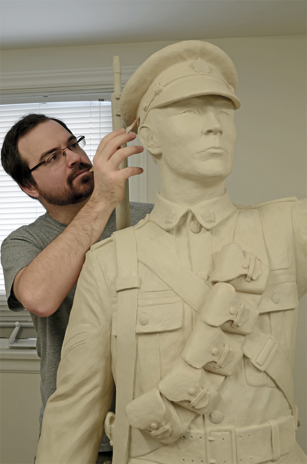 A bearded male sculptor uses a carving tool while he works on a statue of a First World War soldier in a uniform of the time period.