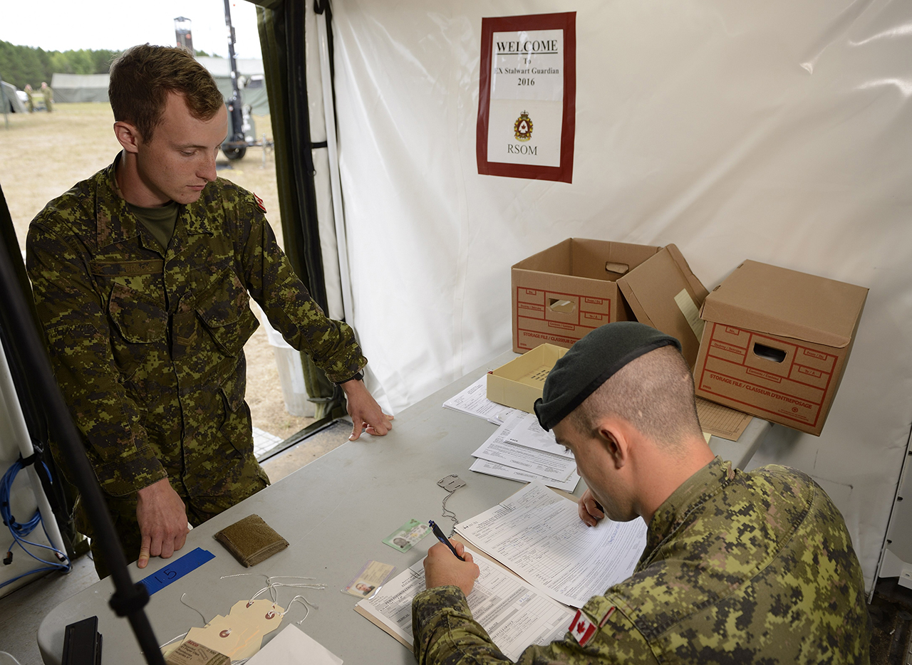 Corporal Brennan Brock completes arrival administrative procedures during Exercise STALWART GUARDIAN on August 14, 2016 at Garrison Petawawa, Ontario.