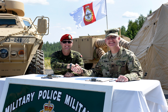 Maj Douglas Henderson (left), 3 Military Police Regiment Commanding Officer and Lieutenant-Colonel James Blake, 211th Military Police Battalion Commander, sign a partnership agreement at Camp Normandy, Base Gagetown during Ex STRIDENT TRACER 16 on August 24, 2016. Photo: WO Jerry Kean