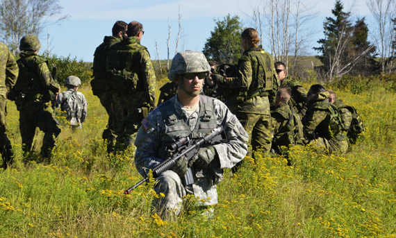 An American MP provides close protection while the Battalion Group Commander is briefed in the field at Base Gagetown, N.B., during Ex STRIDENT TRACER 16 on August 23, 2016. Photo: Lt Felix Odartey-Wellington