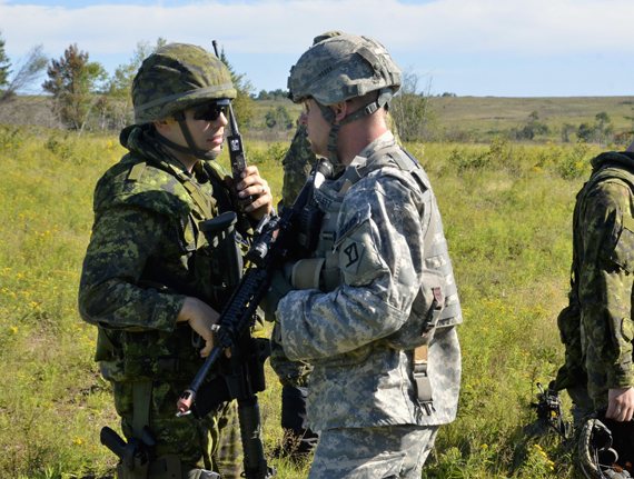 Lieutenant Andrew Wychnenka, 1 Military Police Regiment, discuses security escort routes with Sergeant First Class Joshua Fechter, 91st Military Police Battalion at Camp Normandy, Base Gagetown, during Ex STRIDENT TRACER 16 on August 24, 2016. Photo: WO Jerry Kean