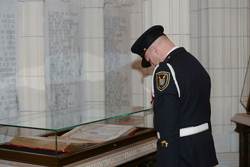 Constable Dale Hins bows his head in solemn contemplation at the Second World War Book of Remembrance in the Memorial Chamber during the daily page turning ceremony on October 19, 2016 in Ottawa, Ontario. 