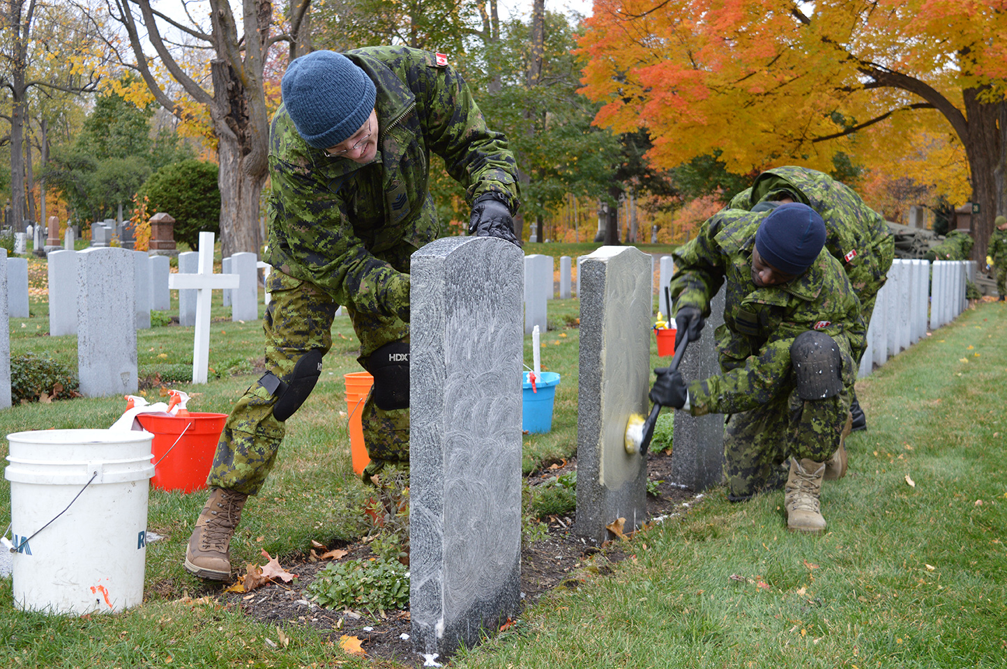 Sergeant Graham Frampton (left), and Captain Alban Massimba clean veterans' headstones at the National Military Cemetery in Ottawa on Oct. 27. Photo by: Jeanne Gagnon, Guard of Honour Newspaper