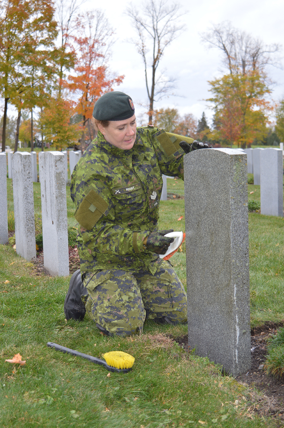 Master Corporal Richelle Provost cleans veterans' headstones at the National Military Cemetery in Ottawa on October 27, 2016.