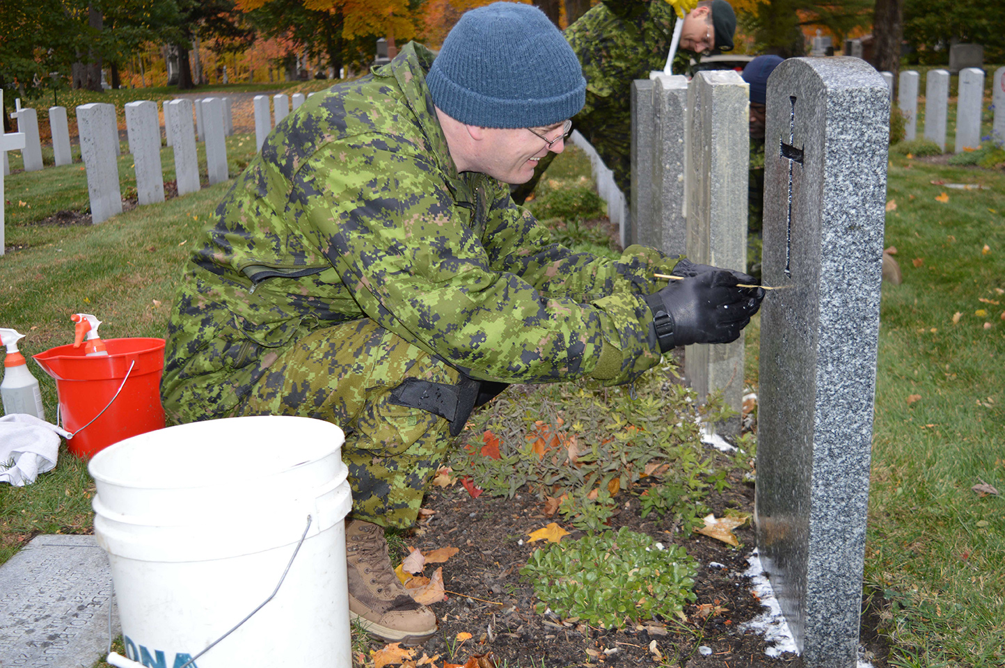 Sergeant Graham Frampton cleans veterans' headstones at the National Military Cemetery in Ottawa on October 27, 2016.
