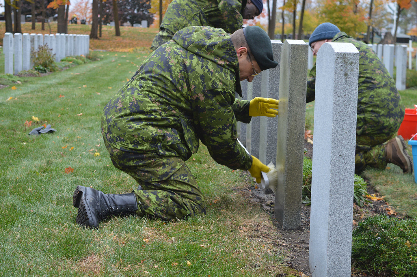Major François Bak cleans veterans' headstones at the National Military Cemetery in Ottawa on Oct. 27. Photo by: Jeanne Gagnon, Guard of Honour Newspaper
