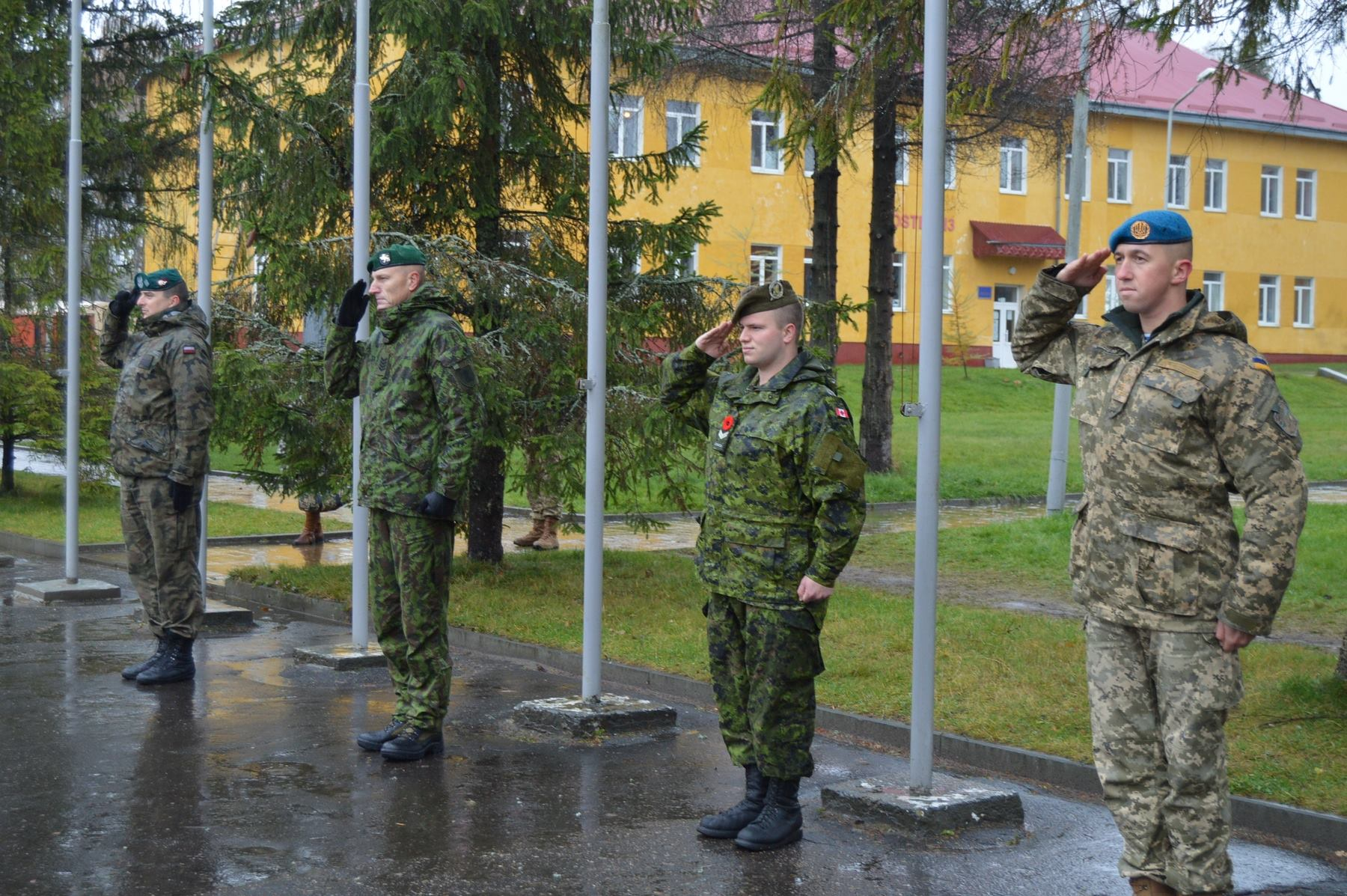 A soldier from Poland, Lithuania, Canada, and Ukraine salute during the national anthems at the opening ceremony for Exercise MAPLE ARCH 16 in YAVORIV, Ukraine on November 7, 2016.