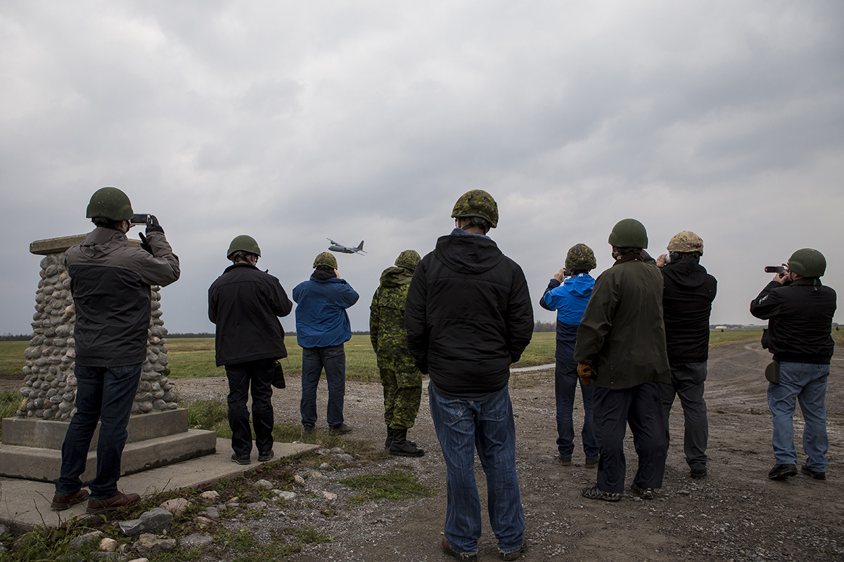 Participants of the Executrek Program watch as a CC-130J Hercules transport plane flies by the Drop Zone at the Drop Zone in Canadian Forces Base Trenton, October 29th 2016.
