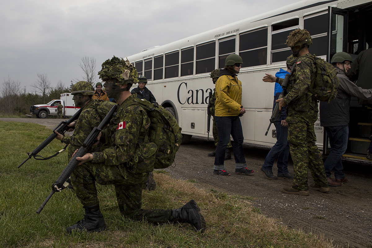Members of The Queens Own Rifles secure the area as participants of the Executrek Program are moved away from the drop zone shack, at the drop zone in Canadian Forces Base Trenton, October 29, 2016.