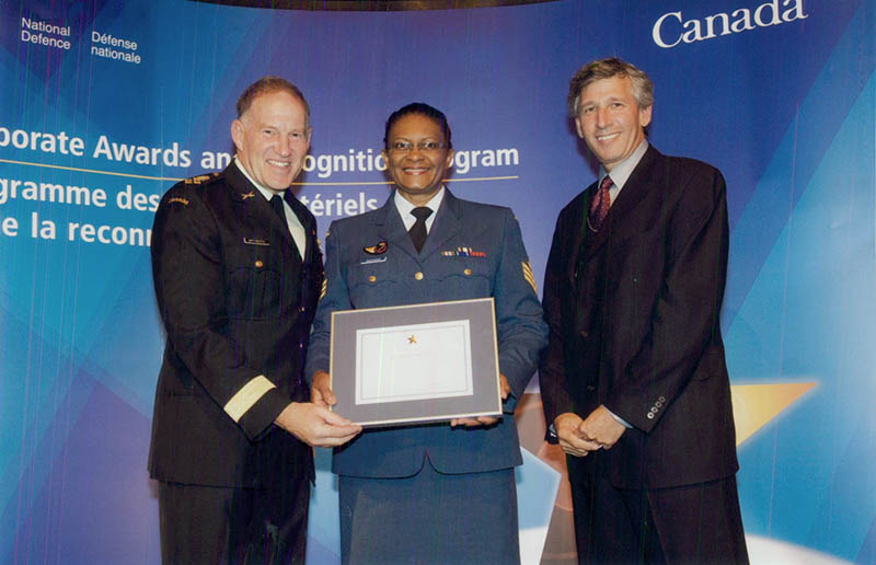 Sergeant Joan Buchanan, now retired, receiving her Corporate Award in Human Resource Management in Ottawa, Ontario in 2009 from General Walter Natynczyk, then-Chief of the Defence Staff and former Deputy Minister of Defence Robert Fonberg.