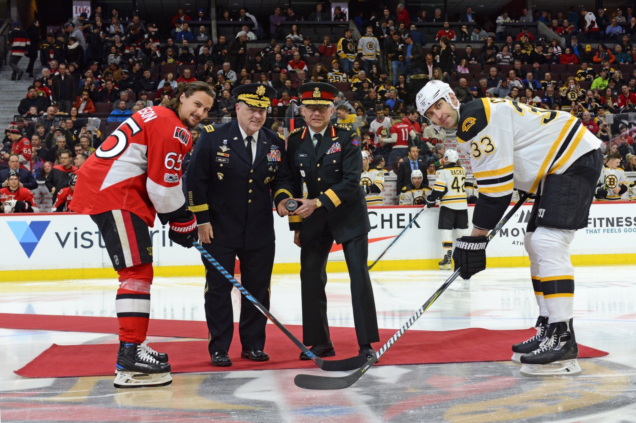 General Mark Milley, Chief of Staff, United States Army (centre-left) and Lieutenant-General Paul Wynnyk, Commander Canadian Army (centre-right) prepare to drop the puck for team captains, Erik Karlsson (left), and Zdeno Chára (right) during the opening ceremonies for the Ottawa Senators vs Boston Bruins hockey game at the Canadian Tire Centre on March 6, 2017. (U.S. Army photo by Sgt. 1st Class Charles Burden)