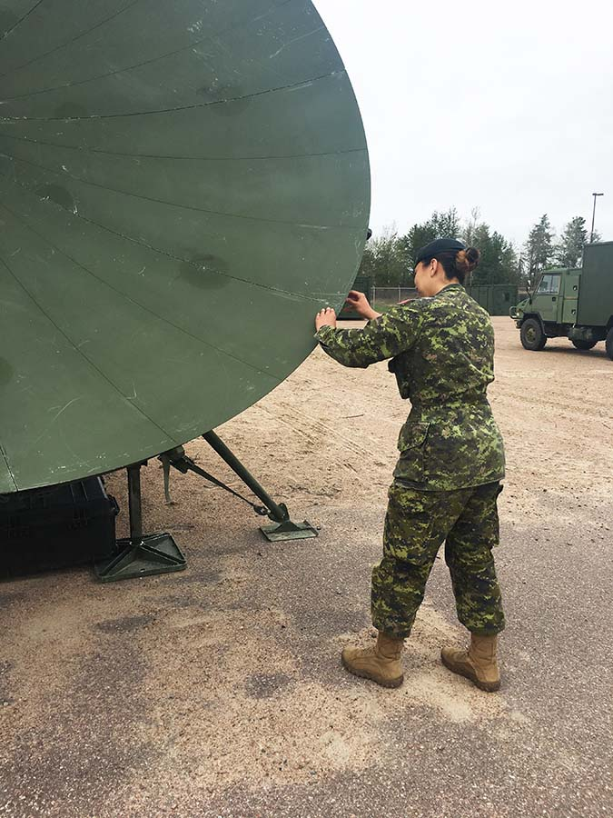 Master Corporal Nikki Gregg, an Army Communication and Information Systems Specialist, sets up a satellite dish at Canadian Forces Base Petawawa, Ontario on May 4, 2017.